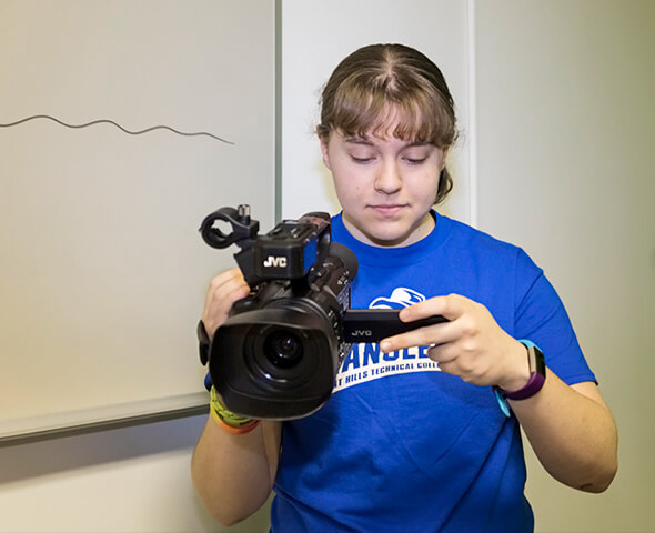 Multimedia Design student holding video camera